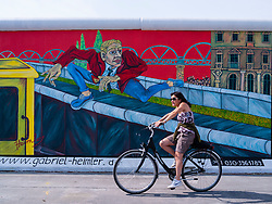 Woman cycles past mural on wall at East Side Gallery at former Berlin Wall in Friedrichshain/Kreuzberg in Berlin Germany