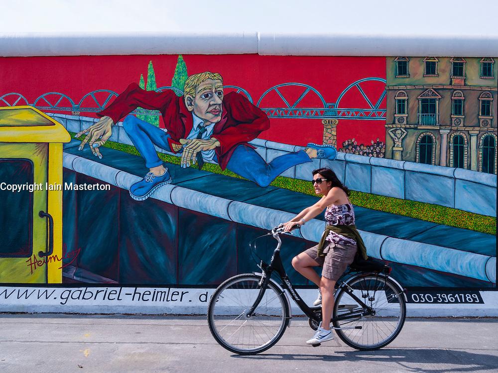 Woman cycles past mural on wall at East Side Gallery at former Berlin Wall in Friedrichshain/Kreuzberg in Berlin Germany