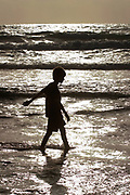 Young boy silhouetted on the beach at sunset