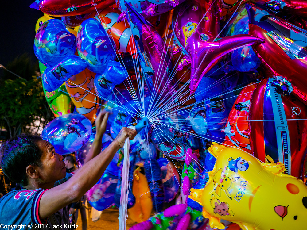 """03 NOVEMBER 2017 - BANGKOK, THAILAND: A vendor sells inflatable toys during Loi Krathong at Wat Prayurawongsawat on the Thonburi side of the Chao Phraya River. Loi Krathong is translated as """"to float (Loi) a basket (Krathong)"""", and comes from the tradition of making krathong or buoyant, decorated baskets, which are then floated on a river to make merit. On the night of the full moon of the 12th lunar month (usually November), Thais launch their krathong on a river, canal or a pond, making a wish as they do so. Loi Krathong is also celebrated in other Theravada Buddhist countries like Myanmar, where it is called the Tazaungdaing Festival, and Cambodia, where it is called Bon Om Tuk.     PHOTO BY JACK KURTZ"""