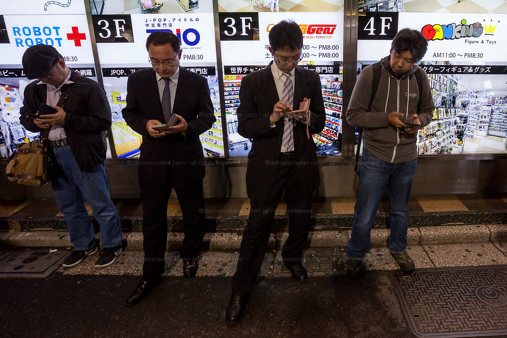 Older and younger Men play Pokemon Go in Akihabara, Tokyo, Japan. Friday October 19th 2018