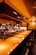 Chef Michihiro Kigawa preparing food at open kitchen and dining counter at Kigawa restaurant.