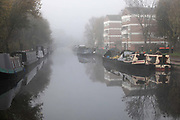 House bouts moored on Regent's Canal on a misty morning on 27th November 2020 in Hackney, London, United Kingdom. The Regent's Canal is a popular place for house boats to moor, particularly this part near Acton's Lock No 7, near Broadway Market in Hackney.