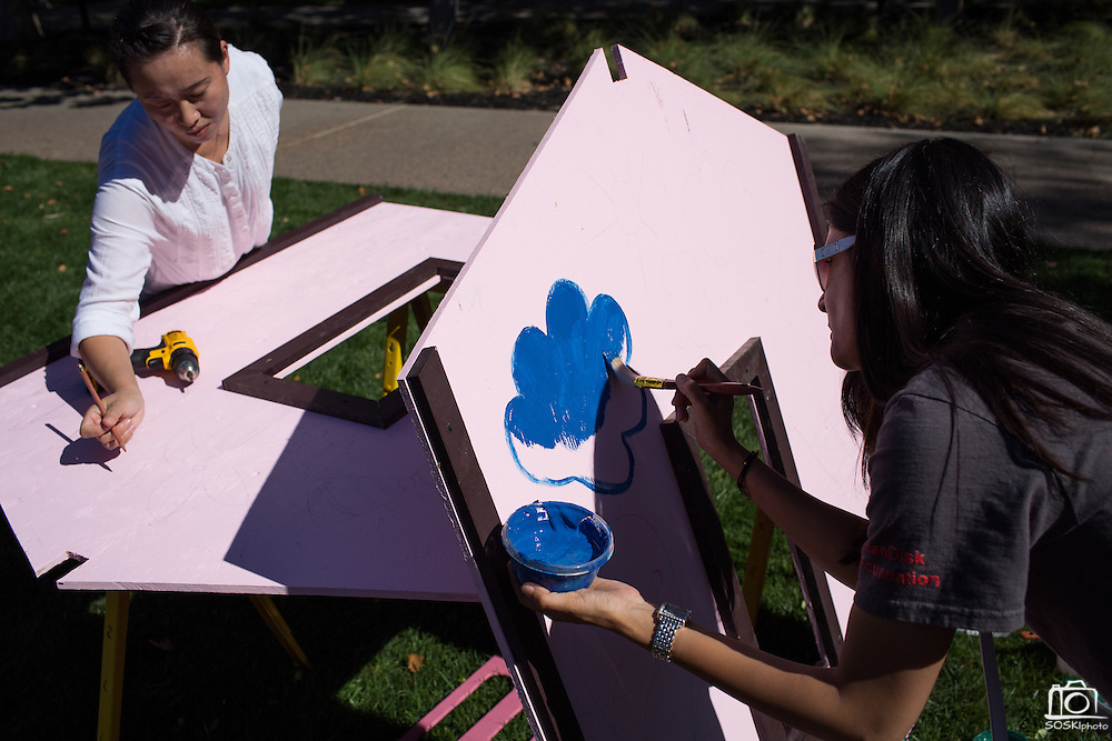 Preeti Yadav paints blue clouds, right, as another SanDisk employee sketches designs on the playhouse walls during a Habitat for Humanity playhouse build at the SanDisk headquarters in Milpitas, California, on August 27, 2013. (Stan Olszewski/SOSKIphoto)