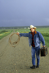 cowboy with a lasso and suitcase hitchhiking on a dirt road in New Mexico