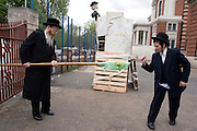 An Orthodox Jewish man with the help of a pupil, from the Bobov School, light a torch. The torch will be used to set alight the Lag B'Omer bonfire in the school playground.  Lag B'Omer is the holiday celebrating the thirty-third day of the (counting of the) Omer. Jews celebrate it as the day when the plague that killed 24,000 people ended in the holy land (according to the Babylonian Talmud). Other sources say the plague was actually the Roman occupation and the 24,000 people died in the second Jewish - Roman war  (Bar Kokhba revolt of the first century).  Bonfires (used as signals in wartime) are symbolically lit to commemorate the holiday of Lag'B'Omer.