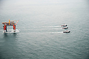 """Deepwater offshore oil platform """"DELTA HOUSE"""" being towed offshore from Kiewit in Ingleside, Texas by Crowley Maritime Corporation's OCEAN CLASS Tugs. (Aerial Photography by Tim Burdick)"""