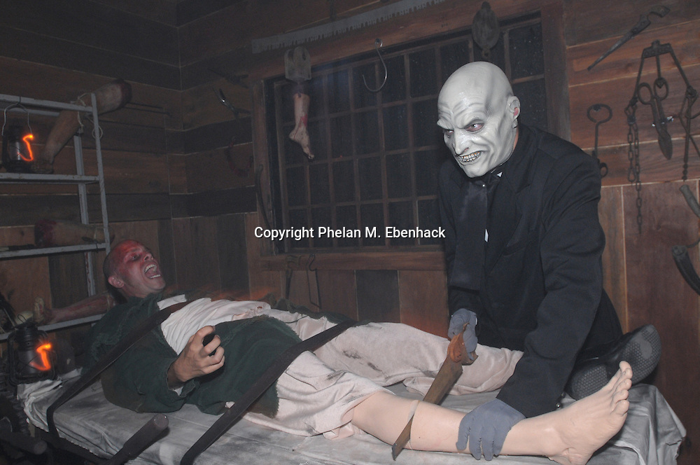 A ghoul saws off the leg of a man in the Body Collectors: Collections of the Past venue during a dress rehearsal of Universal Studios Florida's Halloween Horror Nights in Orlando, Fla., Tuesday, Sept. 16, 2008.