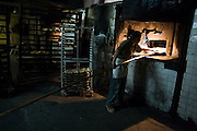A man removes a batch of cookies from the bread oven at Panaderia El Boleo in Santa Rosalia, Baja California Sur, Mexico on January 26, 2009. Founded in 1901 as a French bakery during the years of the French El Boleo Mining Company, it now continues as a Mexican bakery with little change to the building or the equipment.