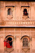 INDIA, RAJASTHAN girls in the carved windows of their home in the ancient city of Jaisalmer, in the  Great Thar Desert