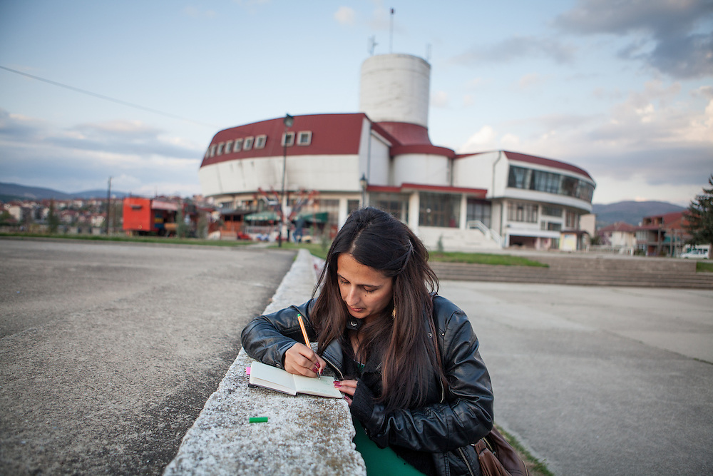 """Romina Kajtazova - working as a paralegal for NGO Kham - writing notes in front of the """"House of Culture"""" in the city of Delcevo in Macedonia."""