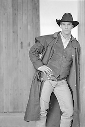cowboy with a gun leaning against a barn wall
