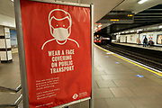 Face covering sign on the station platform at Tower Hill ststion on 3rd July 2021 in London, United Kingdom. As the coronavirus lockdown continues its process of easing restrictions, more and more people are coming to the West End as more businesses open, however many people are still relictant to use public transport and especially the tube.