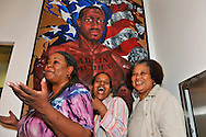 """Three woman members of Citified Book Club, posing for portrait in front of """"Made in America"""" painting, at African American Museum of Nassau County during Family Portrait Day, an event by Long Island Center of Photography, in Hempstead, New York, on September 17, 2011."""