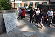City workers take interest in a white-board through Broadgate that purports to be written by a jealous lover to her cheating partner who works nearby but is actually part of a new Dating app start-ups PR stunt in the City of London, the capitals financial district - aka the Square Mile, on 8th August, in London, England.