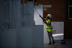 © Licensed to London News Pictures. 12/04/2020. Manchester, UK. Cleaner SAMRAWIT FISSEHA (29) cleaning one of the patient bays . The National Health Service is building a 648 bed field hospital for the treatment of Covid-19 patients , at the historical railway station terminus which now forms the main hall of the Manchester Central Convention Centre . The facility is due to open on Easter Monday , 13th April 2020 , and will treat patients from across the North West of England , providing them with general medical care and oxygen therapy after discharge from Intensive Care Units . Photo credit: Joel Goodman/LNP