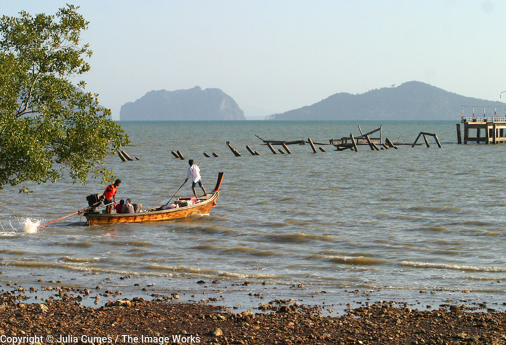 Koh Lanta, Thailand--One of the Hua Laem's few surviving longtail boat heads out for a day of fishing.  Behind it one can see the pier which was destroyed by the Tsunami on Koh Lanta island in Thailand.  Two people were on the pier at the time the waves hit.  One was a villager trying to save his boat and the other was a female tourist who was photographing the wave.  Neither one's body has been found.  01/24/05 © Julia Cumes / The Image Works