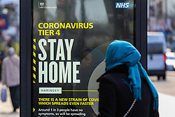 © Licensed to London News Pictures. 02/01/2021. London, UK. A woman in north London looks at the government's 'Coronavirus Tier 4 - Stay Home' publicity campaign poster, after the mutated variant of the SARS-Cov-2 virus continues to spread around the country. The President of the Royal College of Physicians,Professor Andrew Goddard, has warned that COVID-19 infection cases are set to rise in the coming weeks and that NHS staff and healthcare workers are worried about the challenges against the virus over the coming months. Photo credit: Dinendra Haria/LNP