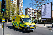 Ambulances on emergency calls leave A&E and pass 'Thank You  to our Awesome NHS' signs and A rhyming message of thanks to key workers, organised by the Out of Home advertising industry, near St Thomas' Hospital - The 'lockdown' continues in London because of the Coronavirus (Covid 19) outbreak.