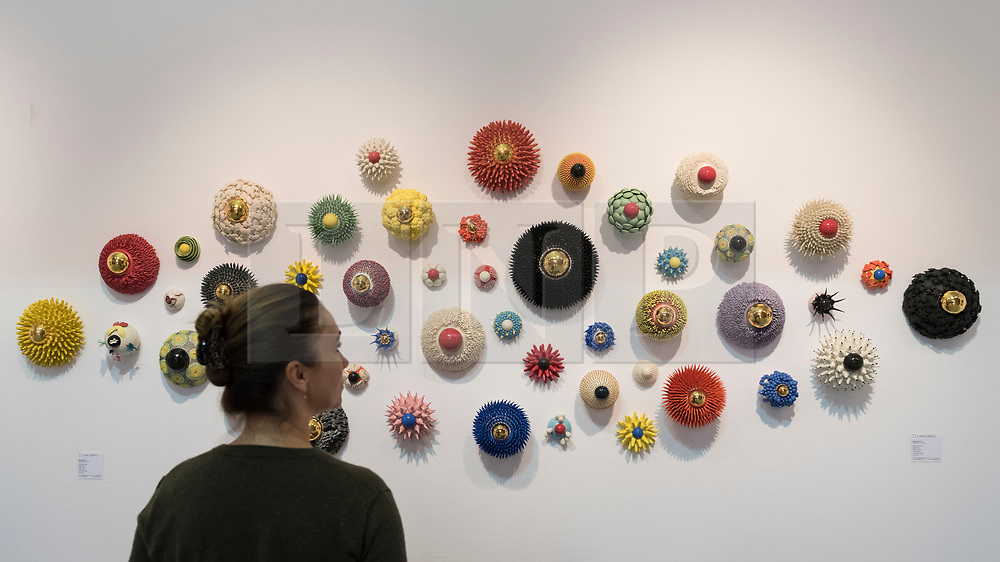 "© Licensed to London News Pictures. 20/06/2018. LONDON, UK. A visitor views ""Eye Series""ceramics by Myung Nam An at The Art & Antiques Fair Olympia which runs 20 to 27 June at Kensington Olympia.  Photo credit: Stephen Chung/LNP"