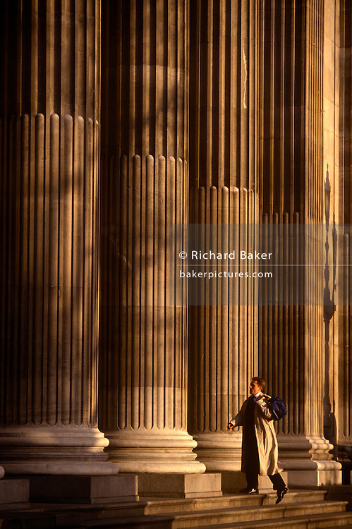 Beneath the sunlit pillars of Trinity Square in the City of London, a businessman strides up the steps with a bag over his shoulder, his long 90s raincoat reaching down to his knees. He may have been delayed, late due to his commuting journey from the suburbs but his arrival at work or meeting seems to a casual deadline.