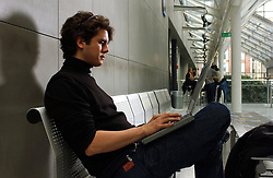 PARIS -  FRANCE - APRIL-21-2004 - Young man alone using a wireless - wifi - laptop computer. (PHOTO © JOCK FISTICK)..technology - business - laptop - notebook - computer - wifi - wireless - internet - communication - email - www - world wide web - web surfing - connect - connecting - connected - connectivity - study - studying - research - academics - education - student - university - young - adult - male - man - think - thinking - concentrate - concentration - concentrating