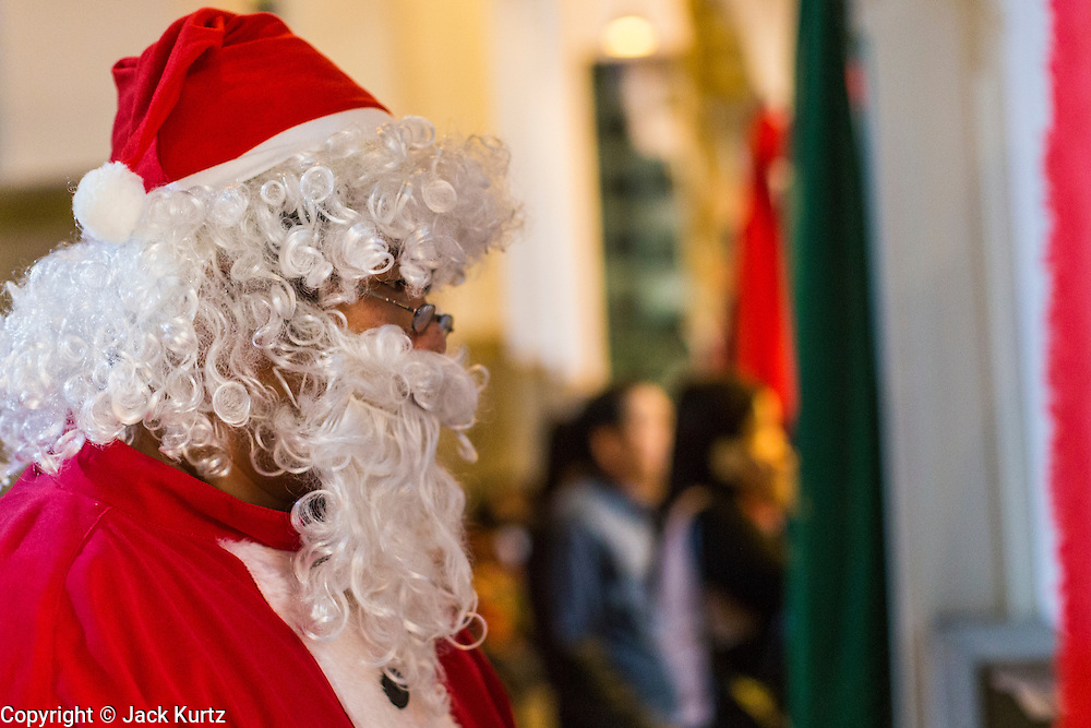 24 DECEMBER 2013 - BANGKOK, THAILAND: Santa Claus gets ready to deliver candy in the church during Christmas services at Holy Redeemer Church in Bangkok. Thailand is predominantly Buddhist but Christmas is widely celebrated throughout the country. Buddhists mark the day with secular gift giving but there are about 300,000 Catholics in Thailand who celebrate religious Christmas. Catholics first came to Thailand (then Siam) in 1567 as chaplain for Portuguese mercenaries in the employ of the Siamese monarchy. There has been a continuous Catholic presence in Thailand since then.   PHOTO BY JACK KURTZ