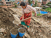 02 AUGUST 2015 - BHAKTAPUR, NEPAL:   A woman digs up dirt for her temporary shelter in a small Internal Displaced Person (IDP) camp in Bhaktapur. Bhaktapur was badly damaged in the earthquake the hit Nepal in April 2015. The Nepal Earthquake on April 25, 2015, (also known as the Gorkha earthquake) killed more than 9,000 people and injured more than 23,000. It had a magnitude of 7.8. The epicenter was east of the district of Lamjung, and its hypocenter was at a depth of approximately 15km (9.3mi). It was the worst natural disaster to strike Nepal since the 1934 Nepal–Bihar earthquake. The earthquake triggered an avalanche on Mount Everest, killing at least 19. The earthquake also set off an avalanche in the Langtang valley, where 250 people were reported missing. Hundreds of thousands of people were made homeless with entire villages flattened across many districts of the country. Centuries-old buildings were destroyed at UNESCO World Heritage sites in the Kathmandu Valley, including some at the Kathmandu Durbar Square, the Patan Durbar Squar, the Bhaktapur Durbar Square, the Changu Narayan Temple and the Swayambhunath Stupa. Geophysicists and other experts had warned for decades that Nepal was vulnerable to a deadly earthquake, particularly because of its geology, urbanization, and architecture.      PHOTO BY JACK KURTZ