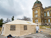 "16 MARCH 2020 - DES MOINES, IOWA: A public health employee in protective clothing at the health screening tent on the east lawn at the Iowa State Capitol in Des Moines. Because of numerous reports of Coronavirus in Iowa, the governor is suspending the legislative session for 30 days. It was scheduled to run until mid-April. Sunday night, the Governor announced that the state health department had recorded ""community spread"" in Des Moines. As a result the State Capitol instituted mitigation measures that included mandatory health screening for everyone going into the building, canceling group tours of the building, and closing the souvenir shop and snack bar.       PHOTO BY JACK KURTZ"