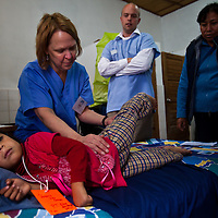 Occupational Therapist Andrea Serdar tests the range of the young girl's leg. Oregon orthopedic doctors and support staff helped hundreds of Peruvian children in Coya, Peru performing corrective surgeries and therapy to improve their quality of life.