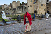 A tourist lady covers her head with a red coat while others  wearing rain-proof capes walk in front of the Tower of London, on 14th September 2017, in London, England. Over many centuries, the Tower saw countless executions and beheadings of those accused and tried of treason and crimes against the state.