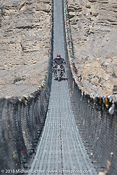 Rip Rolfsen riding across a narrow suspension bridge over the Kali Gandaki River on day-6 of our Himalayan Heroes adventure riding from Muktinath to Tatopani, Nepal. Sunday, November 11, 2018. Photography ©2018 Michael Lichter.