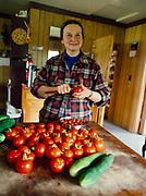 Chulitna Bay resident Sara Hornberger slicing tomatoes from her greenhouse, Koksetna Camp, Lake Clark, Lake Clark National Park and Preserve, Alaska.