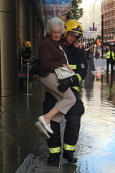 © Licensed to London News Pictures. 07/06/2015. London, UK. VIDEO AVAILABLE<br />  A fireman carries a woman through floodwater in Victoria, central London. Victoria Street flooded due to a burst water main on Saturday causing several business, including the Curzon Cinema to be evacuated. Photo credit : Susie Stringfellow/LNP
