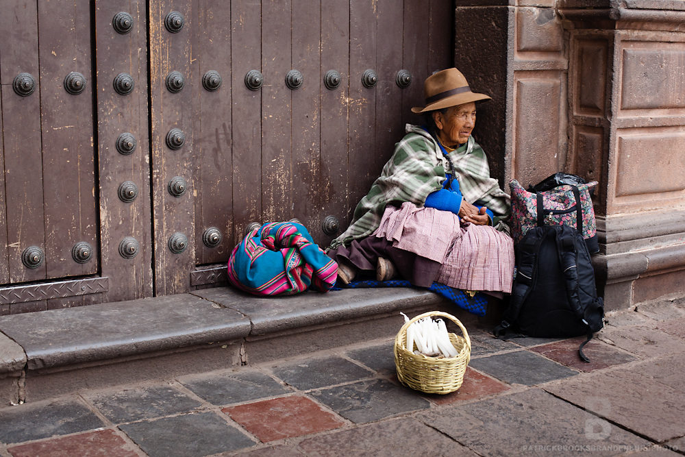 A peruvian women in traditional clothing sits in front of Cathedral with a mixture of traditional and contemporary bags as well as a basket of candels in Cusco, Peru.