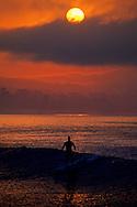 Surfer at sunrise in Monterey Bay near Capitola Beach, Santa Cruz County, CALIFORNIA