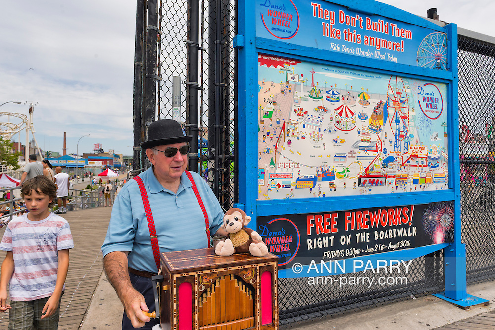 Brooklyn, New York, USA. 10th August 2013. Organ grinder BILL SHARKEY is playing the Jager & Brommer Organ, on the boardwalk next to a sign with a diangram of Coney Island amusement park on it, during the 3rd Annual Coney Island History Day celebration. Sharkey and the other organ grinders participating that day are members of AMICA.
