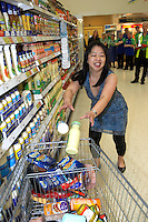 oriental lady rushing around a supermarket buying food products