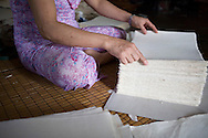 Cham Khe village is specialised in the production of paper. Worker sorting sheets of paper.