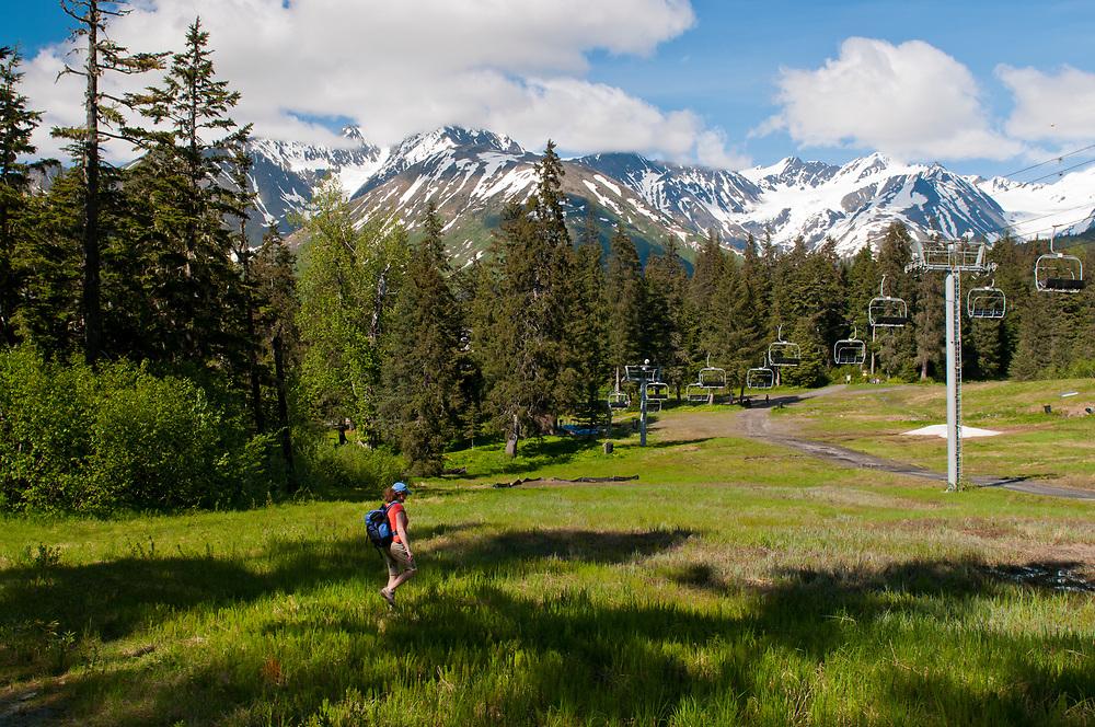 Alaska, Girdwood, Mt Alyeska. A woman  enjoy the wonderful grounds  beneath Chair 7 in summer.