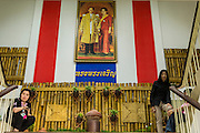 """01 FEBRUARY 2014 - BANGKOK, THAILAND:  Election workers hide from voters under a portrait of Bhumibol Adulyadej, the King of Thailand, and his wife Queen Sirikit while protesting voters try to get into the polling place in Din Daeng. Thais went to the polls in a """"snap election"""" Sunday called in December after Prime Minister Yingluck Shinawatra dissolved the parliament in the face of large anti-government protests in Bangkok. The anti-government opposition, led by the People's Democratic Reform Committee (PDRC), called for a boycott of the election and threatened to disrupt voting. Many polling places in Bangkok were closed by protestors who blocked access to the polls or distribution of ballots. The result of the election are likely to be contested in the Thai Constitutional Court and may be invalidated because there won't be quorum in the Thai parliament.   PHOTO BY JACK KURTZ"""