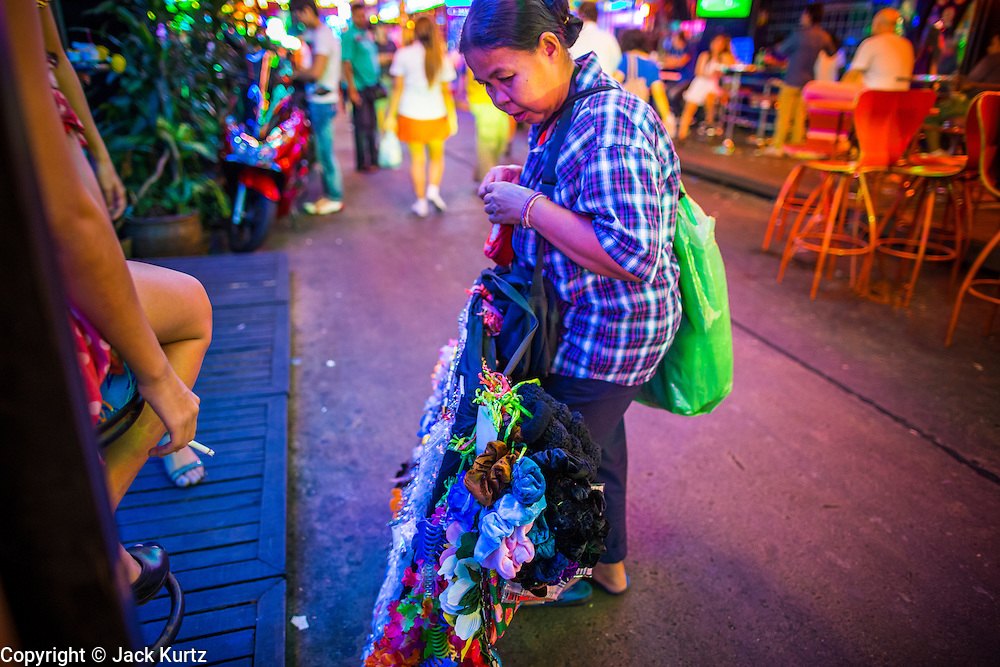 """12 JANUARY 2013 - BANGKOK, THAILAND:  A woman who sells garters to entertainers in Soi Cowboy red light district show her products to """"ladyboy"""" (transgendered) entertainers on the Soi. In Thai, the ladyboys are called kathoey. Many work in the entertainment and night life sectors of the Thai economy. Prostitution in Thailand is illegal, although in practice it is tolerated and partly regulated. Prostitution is practiced openly throughout the country. The number of prostitutes is difficult to determine, estimates vary widely. Since the Vietnam War, Thailand has gained international notoriety among travelers from many countries as a sex tourism destination. One estimate published in 2003 placed the trade at US$ 4.3 billion per year or about three percent of the Thai economy. It has been suggested that at least 10% of tourist dollars may be spent on the sex trade. According to a 2001 report by the World Health Organisation: """"There are between 150,000 and 200,000 sex workers (in Thailand).""""    PHOTO BY JACK KURTZ"""