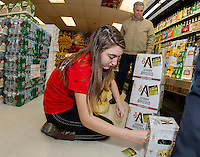 """Brooke D'Amico places stickers on alcoholic beverage packaging with Brian Loanes during the """"Sticker Shock"""" program on Thursday morning at Vista Foods.  (Karen Bobotas/for the Laconia Daily Sun)"""