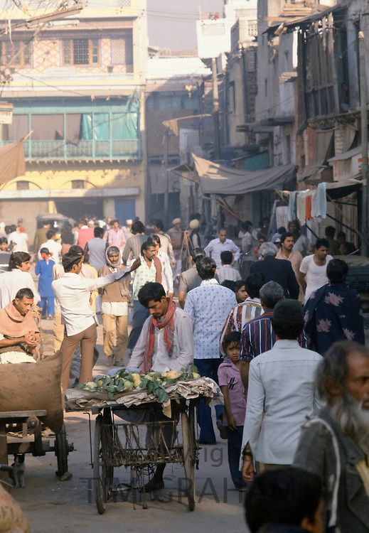 Food sellers and shoppers in busy street market in Delhi, India