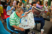 11 JULY 2011 - BANGKOK, THAILAND:   Passengers read newspapers while they wait for their trains in Hua Lamphong station in Bangkok. Hua Lamphong Grand Central Railway Station, officially known as the Bangkok Grand Central Terminal Railway Station, is the main railway station in Bangkok, Thailand. It is located in the center of the city in Pathum Wan District, and is operated by the State Railway of Thailand. The station was opened on 25 June 1916, after six years' construction. The station was built in an Italian Neo-Renaissance style, with decorated wooden roofs and stained glass windows. The architecture is attributed to Turin-born Mario Tamagno, who, with countryman Annibale Rigotti made a mark on early 20th century public building in Bangkok. The pair also designed Bang Khun Prom Palace (1906), Ananda Samakhom Throne Hall in The Royal Plaza (1907-15) and Suan Kularb Residential Hall and Throne Hall in Dusit Garden, among other buildings..There are 14 platforms and 26 ticket booths. Hua Lamphong serves over 130 trains and approximately 60,000 passengers each day. Thailand has the most advanced rail system in Southeast Asia and trains from Hua Lamphong serve all corners of the Kingdom.       PHOTO BY JACK KURTZ