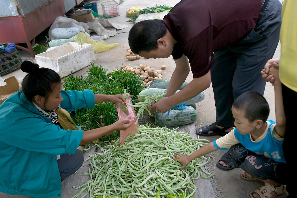 Visiting their town market, Cui Haiwang chooses string beans while his wife and son watch. (Supporting image from the project Hungry Planet: What the World Eats.) The Cui family of Weitaiwu village, Beijing Province, China, is one of the thirty families featured, with a weeks' worth of food, in the book Hungry Planet: What the World Eats.