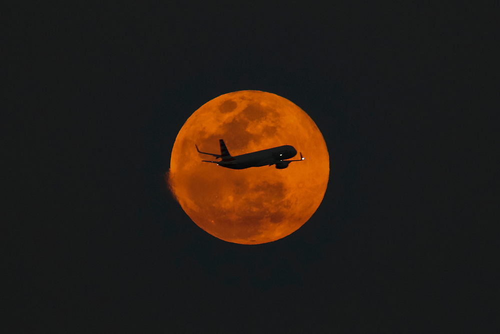 An American Airline A321 departs Miami International Airport in front of the rising full moon.