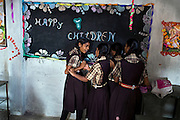 On Children's Day 2014, November 14, 2014, Poonam's sister Jyoti, 13, is arguing with a classmate over a piece of chalk, while playing around near a blackboard inside the cozy, private school Poonam and she regularly attend since 2011, located by their newly built home in Oriya Basti, one of the water-contaminated colonies in Bhopal, central India, near the abandoned Union Carbide (now DOW Chemical) industrial complex, site of the infamous '1984 Gas Disaster'. The two girls are studying in Year 6, out of 12, in 2015-16.