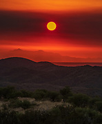 Smoke from the Bighorn Fire, burning in the Santa Catalina Mountains north of Tucson, filters the sun shortly after dawn as seen from the grasslands north of Greaterville, Arizona, USA, on June 23, 2020. The lightning-sparked wildfire started on June 5 and, as of the 23rd, burned over 58,000 acres and was 33% contained.
