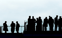 Racegoers in silhouette during St Patrick's Thursday of the 2018 Cheltenham Festival at Cheltenham Racecourse.